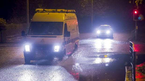 An ambulance drives past a flooded part of the road in Glasgow as Storm Abigail hits the UK