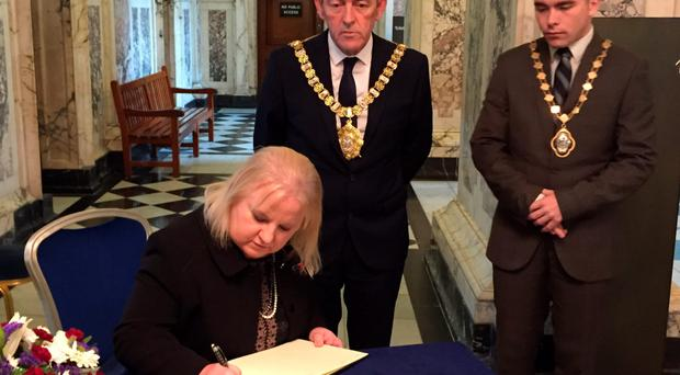 Lord Mayor Arder Carson looks on as French Consul Regine McCullough signs a book of condolence