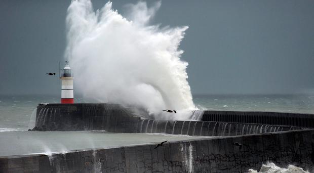 Waves crash into the lighthouse in Newhaven, East Sussex, yesterday as Storm Barney hit Britain