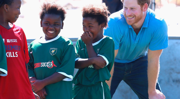 Prince Harry laughs with young girls during a visit to a Football for Hope session in Cape Town as part of his tour of South Africa
