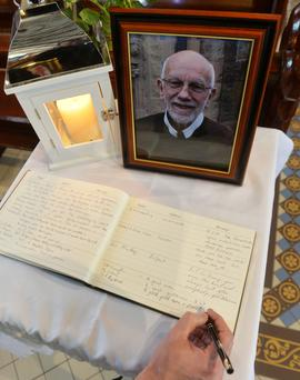 A mourner signs the book of condolence for Fr Gerry Reynolds at Clonard Monastery