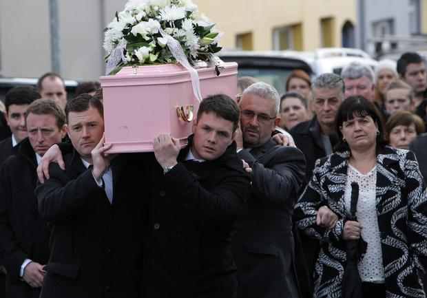 The pink coffin of little Eva Tomney is carried from St Patrick's Church in Keady