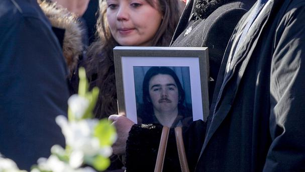 A family member holds an image of Disappeared victim Brendan Megraw following his funeral mass last year