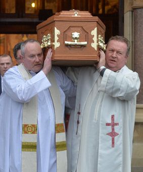 The coffin of Father Gerry Reynolds is carried from Clonard Monastery following his funeral service yesterday