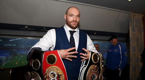 Tyson Fury holds his belts during a homecoming event at the Macron Stadium, Bolton.