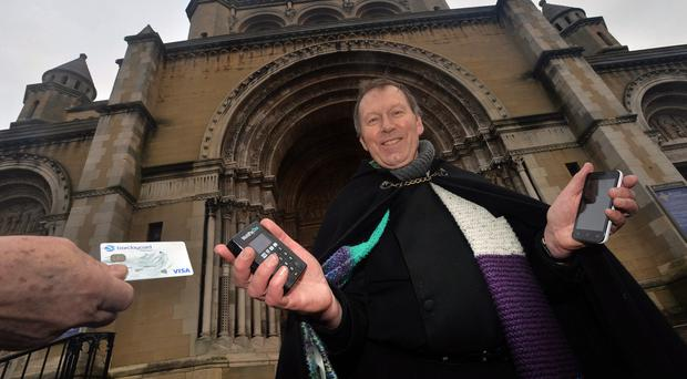 Charity mission: Dean John Mann with his new card reader begins the annual Belfast Black Santa sit-out
