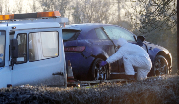Police forensics officers remove the vehicle in which PSNI officer Peadar Heffron was injured in a car bomb explosion on the Milltown Road in Co Antrim, in 2010
