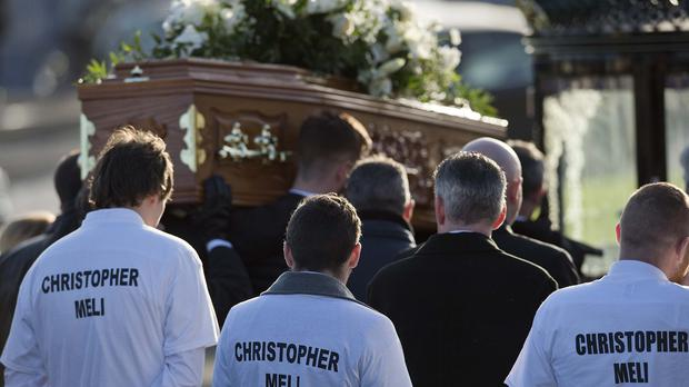 The coffin of Christopher Meli is carried during his funeral in Belfast