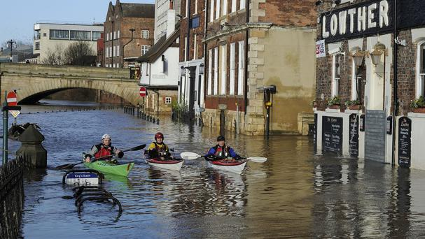 People use canoes in York as levels on the River Ouse remain high after recent severe flooding in the city centre