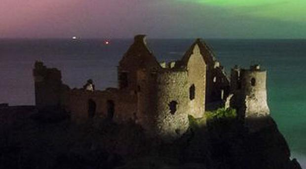The Aurora Borealis, or Northern Lights, was captured by Enda McAuley over Dunluce