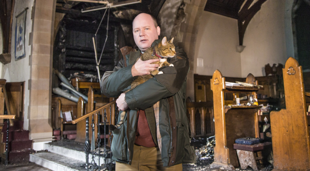 Rev Adrian McLaughlin and his cat Tilly inside St Colman's Church in Dunmurry yesterday