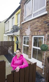 Biddy Ward outside her paint-spattered home in Newry
