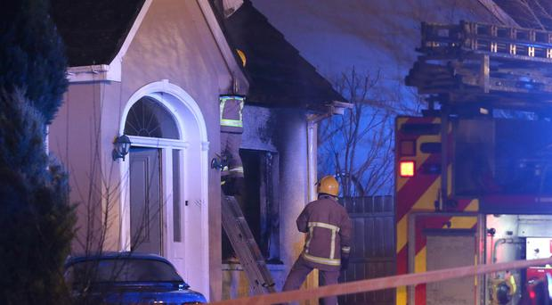 Firefighters tackle the fire at a detached house in Woodcroft Brae in Ballymena