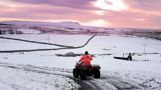 A man rides a quad bike during sunrise over the high ground of the Yorkshire Dales