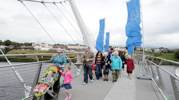 People walking across the 235-metre Peace Bridge across the River Foyle
