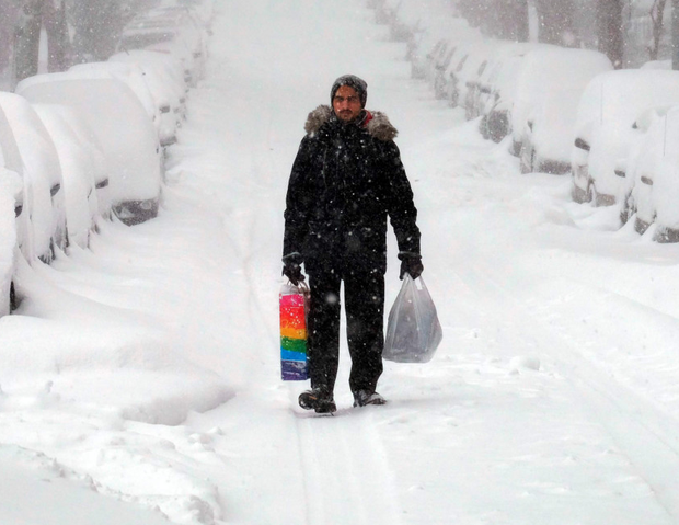 A man makes his way home with some shopping during the snowstorm in New York