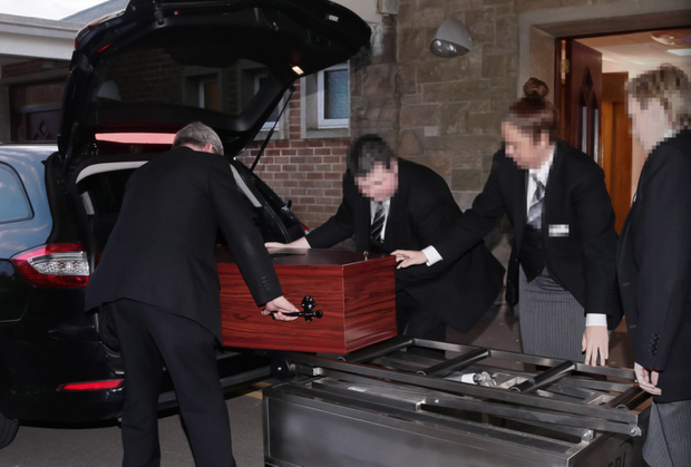 The coffin of Robert Black arriving and being handled at Roselawn yesterday