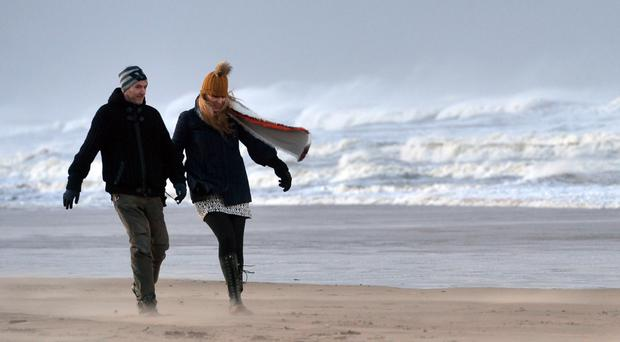 A couple battle against the powerful winds along the Strand