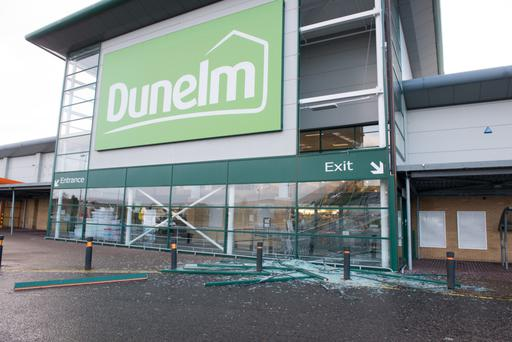 A shattered window panel is strewn across the ground after being torn from the Dunelm store in Londonderry on Monday
