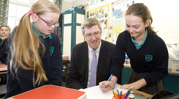 Education Minister John O'Dowd with pupils Lauren Armstrong and Emma Craig during a visit to Strandtown Primary School in 2013