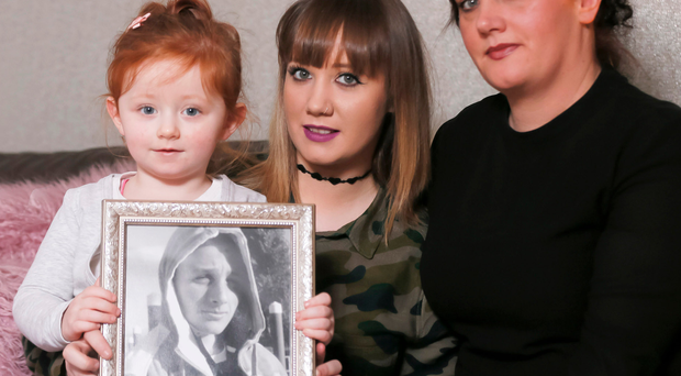 Ryan Quinn's mother Lisa Johnston (40) and daughters Zara Quinn (20) and Layla Ryanne Johnston (2) display a picture of Ryan who died after being struck by a train seven years ago