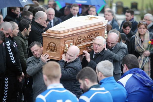 Mourners carry Mark's coffin