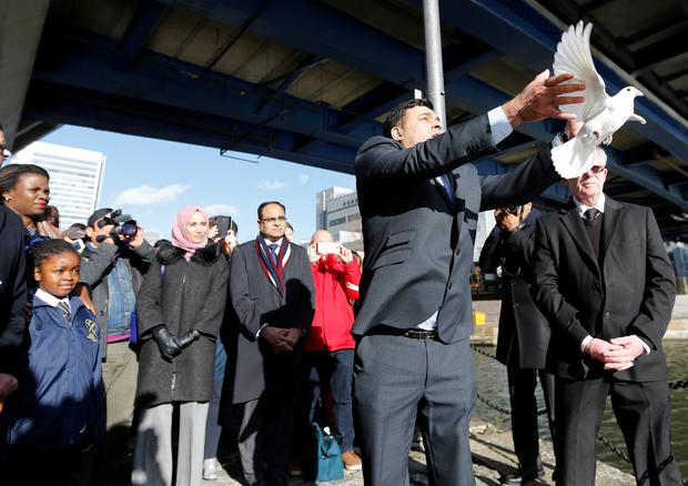 Jonathan Ganesh releases a dove at the memorial service at South Quay station attended by survivors and emergency services