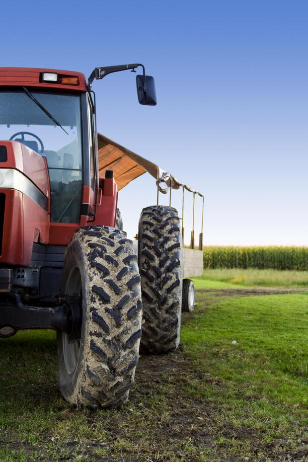A tractor in a field, and (right) John Henning, Danske's head of agricultural relations