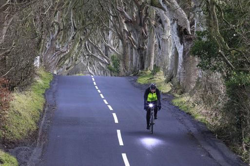 A man cycles through the Dark Hedges