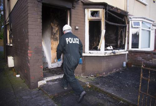 A police officer enters the fire-damaged house at Glencairn Crescent
