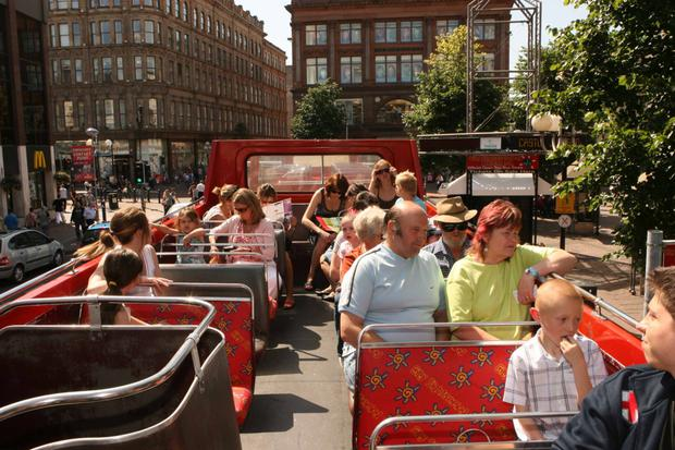 A tour bus takes sightseers through Belfast city centre — but there are fears operators are too aggressive when trying to attract customers