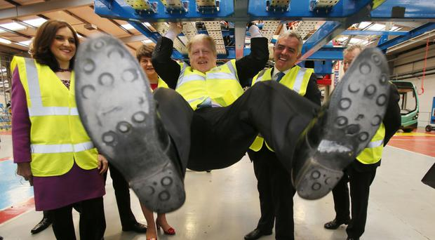 Mayor of London Boris Johnson swings from a bus during a visit to Wrightbus in Antrim