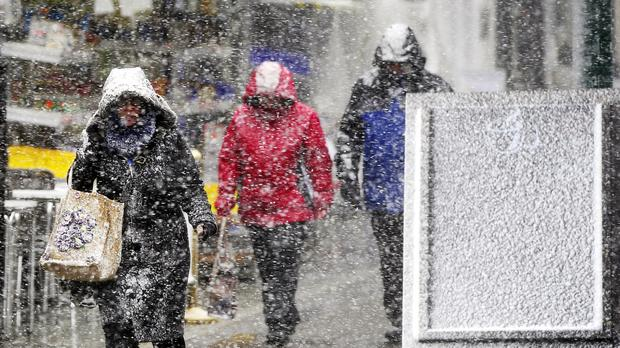People makes their way through Buxton town centre in Derbyshire as snow falls