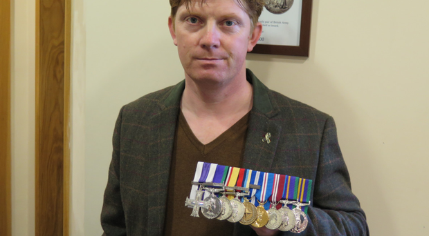 Sgt Trevor Coult with the medals he has put up for auction