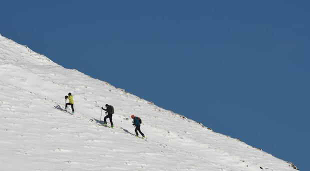 Walkers make their way through the snow near Mam Tor in the Peak District