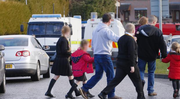 Parents collect their children yesterday after Christ the Redeemer Primary School in Dunmurry was evacuated