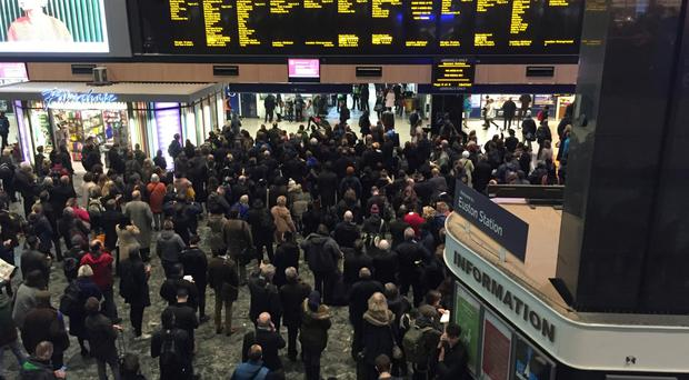 Passengers crowd the concourse at Euston station in London as heavy flooding led to severe rail disruption and overcrowding at the station.