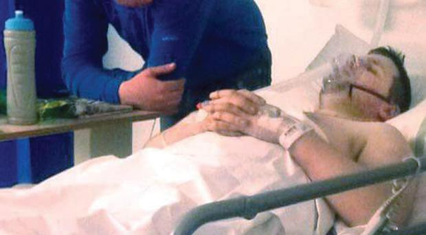 Aidan Doherty watches over twin brother Dean, who was injured riding a motorbike
