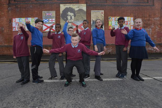 Pupils from Fane Street and Donegall Road Primaries in front of the mural of St Patrick