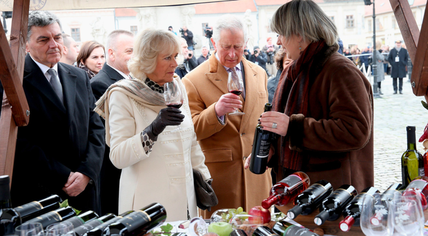The Prince of Wales and the Duchess of Cornwall taste wine as they visit market stalls in the town square in Osijek