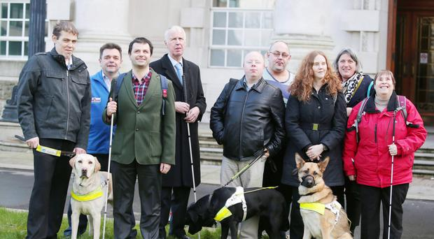 Joanna Toner (third from right) with her guide dog and some of her supporters outside the High Court