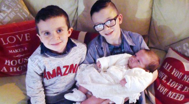 Mark McGrotty, right, and his brother Evan pictured holding their baby sister Rionaghac-Ann