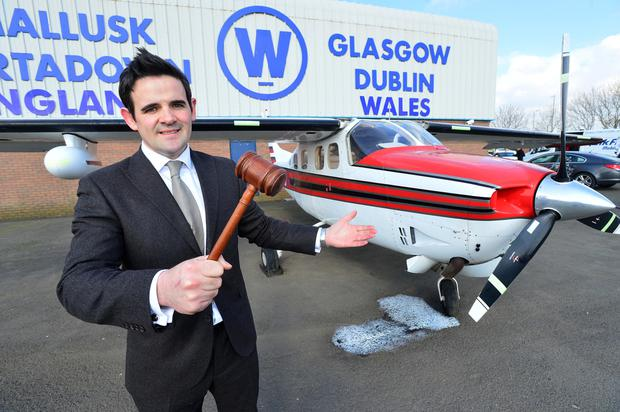 Wilsons Auctions' Aidan Larkin with the Cessna airplane which will be up for grabs