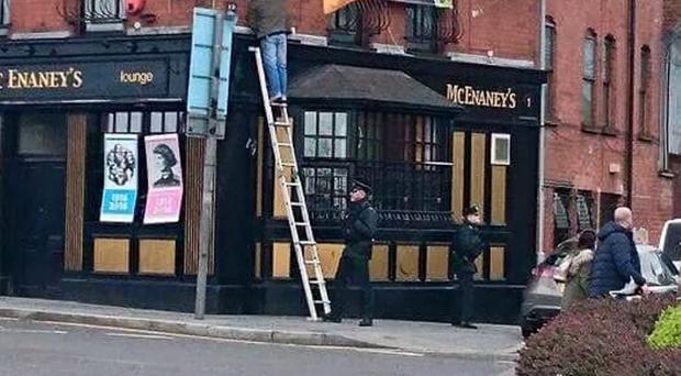 Social media image of a PSNI officer supporting a ladder for a man raising a flag on the Glen Road, Belfast