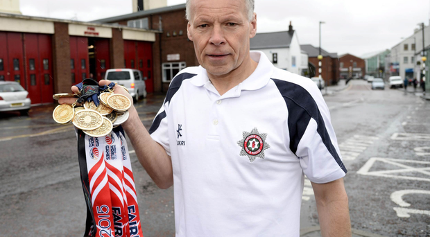 Gary Davison with the medals he won at the World Police and Fire Games, and (left) on the podium