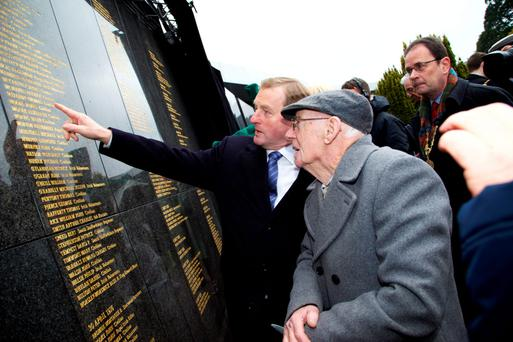 Acting Taoiseach Enda Kenny with Thomas Murphy (95), whose great-uncle Thomas Meleady is named on the wall