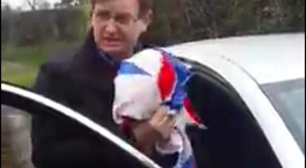 Mr Frazer is stopped by a bogus policeman... who tells him: 'Put your flag away, good man'