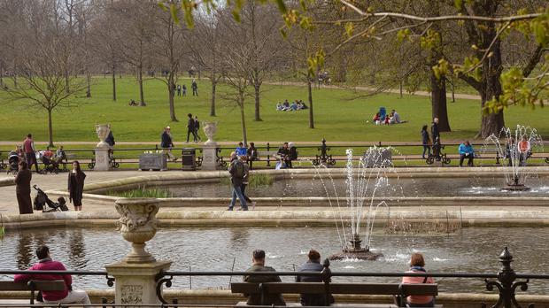People enjoy the warm weather in Kensington Gardens, London