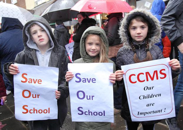 Parents and children braved heavy rain to protest over ongoing problems at De La Salle College in west Belfast