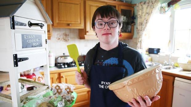 Ryan Bogues, 21, with his cookie box at his home in Ballynahinch, Co Down